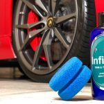 A bottle of Prima Infinity Tire Cream sits in front of a red car