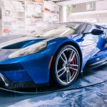 A blue sports car is washed in a garage
