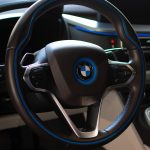 A black BMW steering wheel with blue highlights is displayed