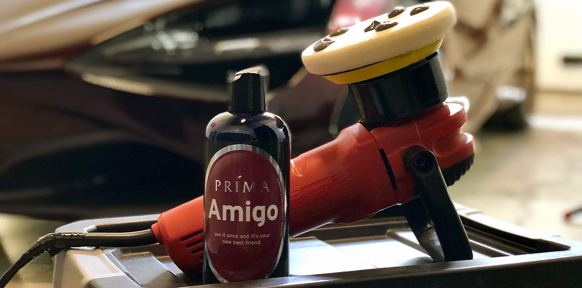 A bottle of Prima Amigo auto polish sits in front of a polisher