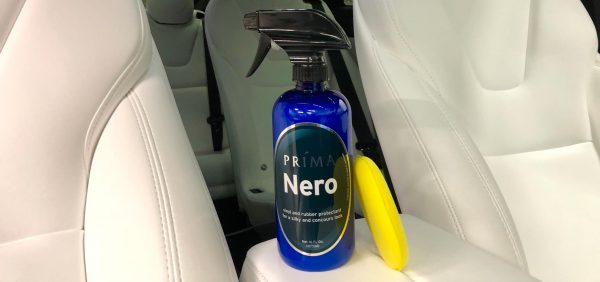 A bottle of Prima Nero car care product sits on the console of a white vehicle interior