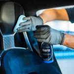 A man polishes a vehicle seat headrest with a bottle of Prima Nero