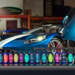 The full line of Prima Car Care products sit in a row in front of a blue sports car