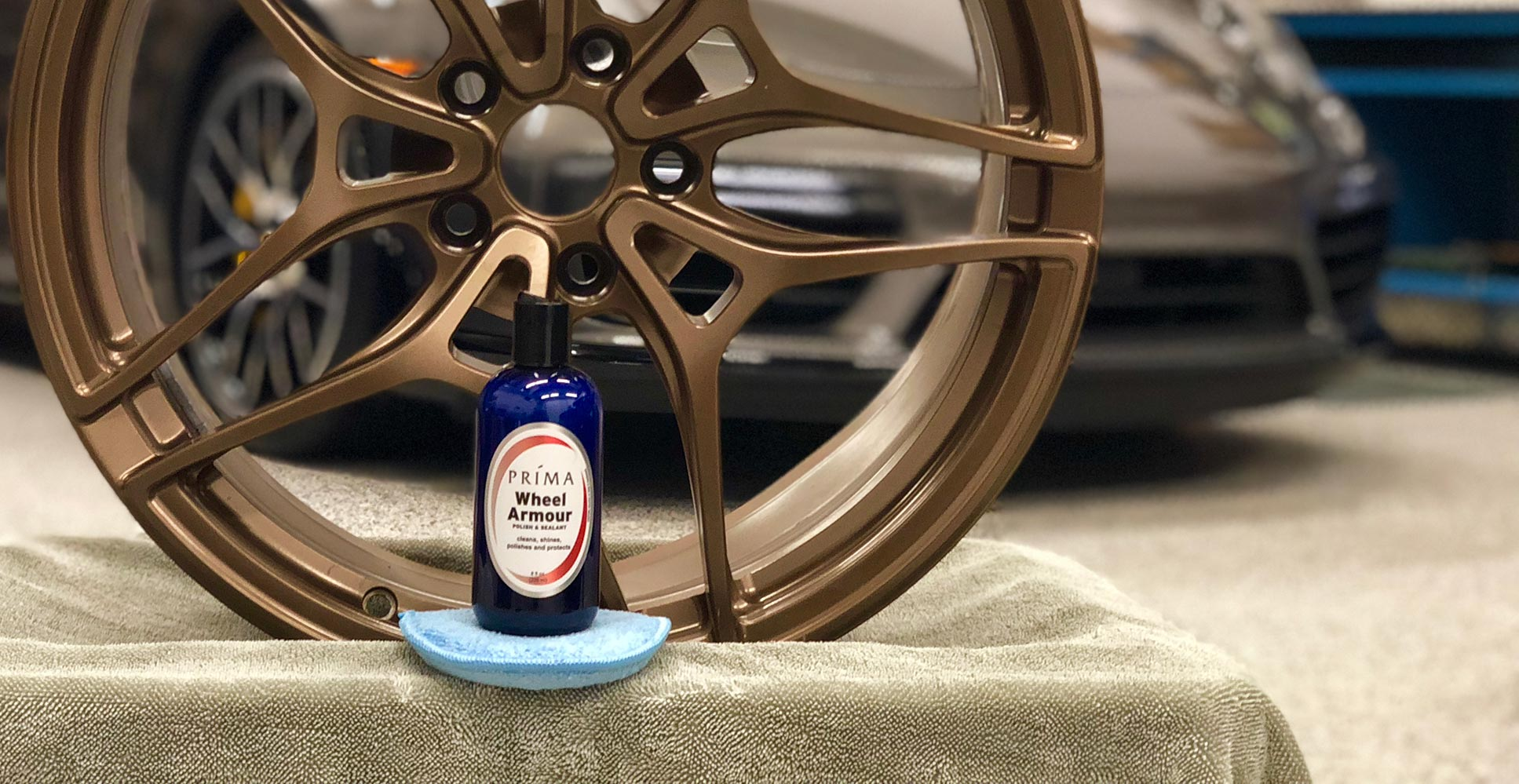 A bottle of Prima Wheel Armour wheel cleaner sits in front of a tire rim